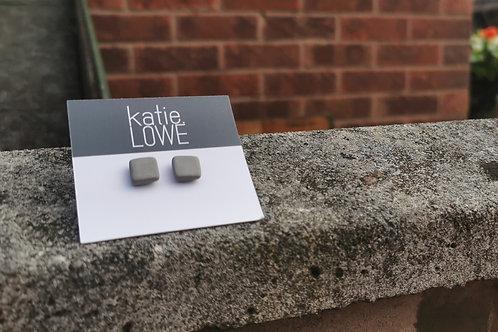 square grey stud earrings.