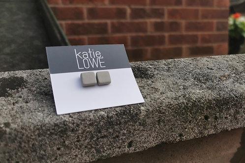 square pale grey stud earrings.