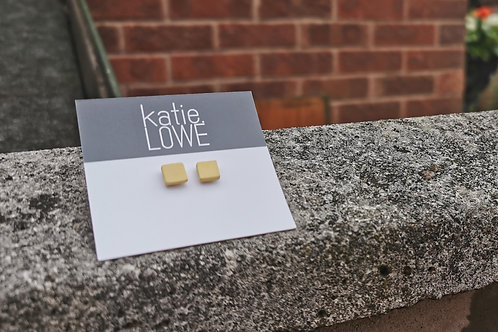 tiny square yellow stud earrings.