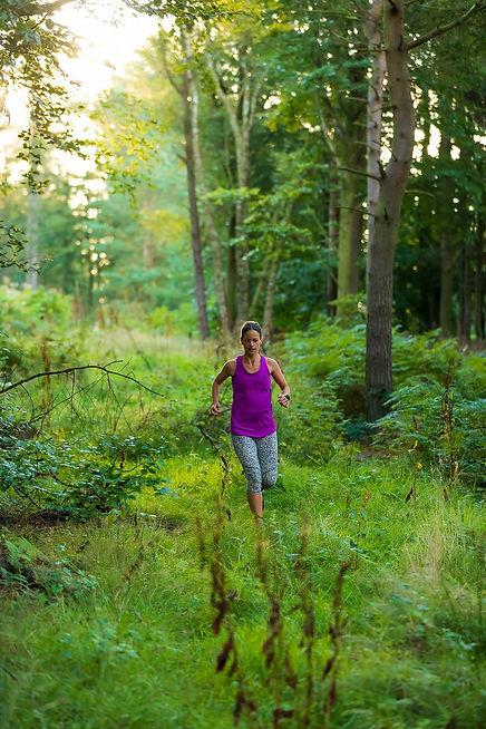 woman running through woods