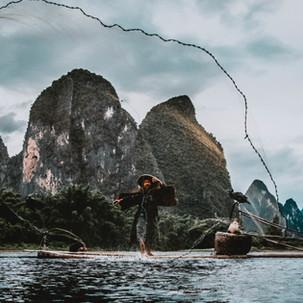 Cormorant fisherman throwing his net.