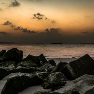 Rocks, sand, sea and sky.