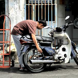 Moto repairing in Penang streets.