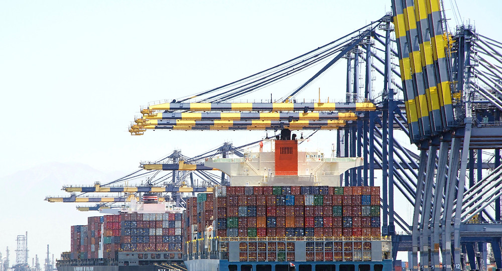 Large cargo cranes at a shipping port, taking containers from vessels
