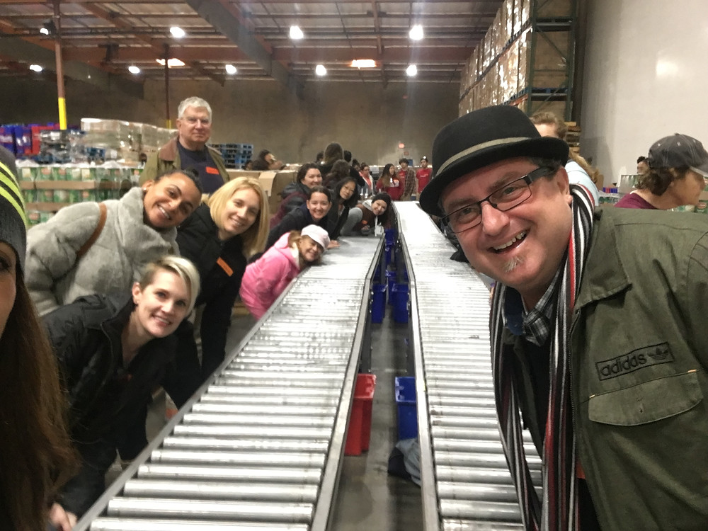 The Novak Law team standing over two conveyor belts and smiling at the L.A. Food Bank warehouse