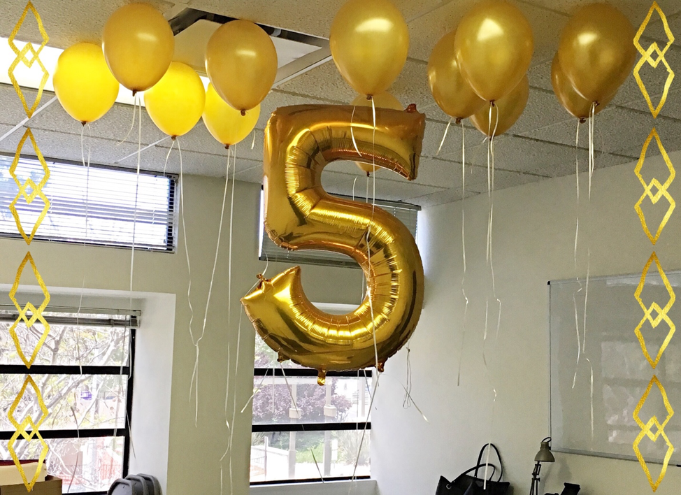 A balloon shaped like the number 5 and other celebration balloons and streamers to depict a 5-year anniversary celebration