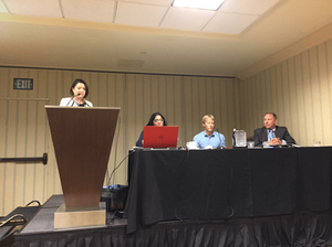 Jennifer Novak and three other people on a stage lecturing an audience at a conference
