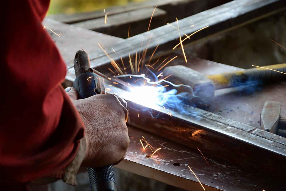 A man's arm holding welding tools, welding a metal frame