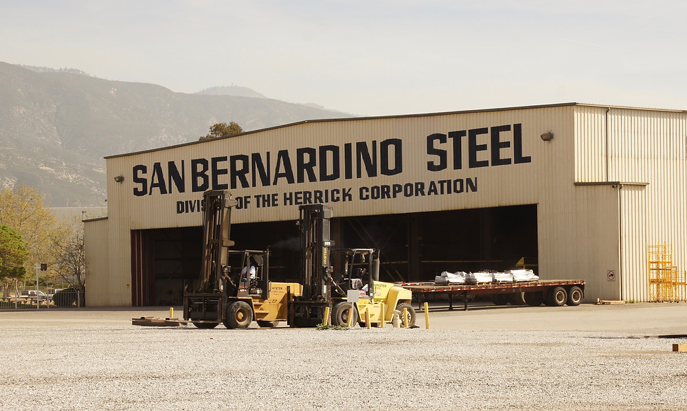 The San Bernardino Steel warehouse building and two forklifts for the steel fabrication facility, with mountains in the distance