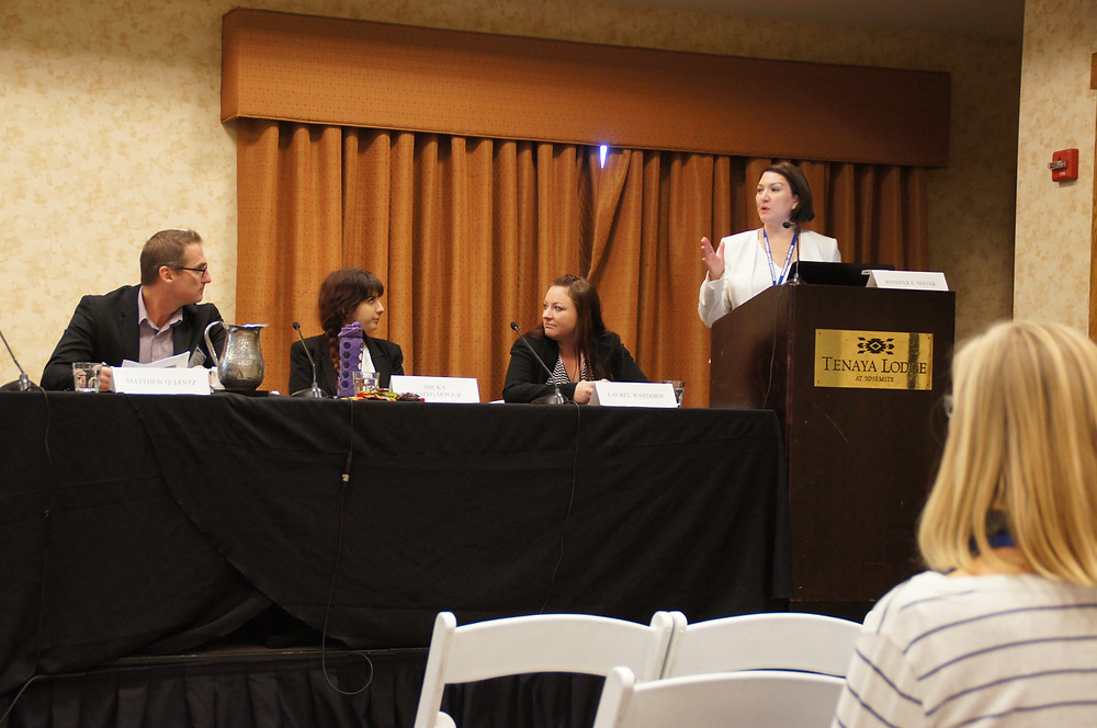 Jennifer Novak and three other people on stage lecturing an audience at a law conference.