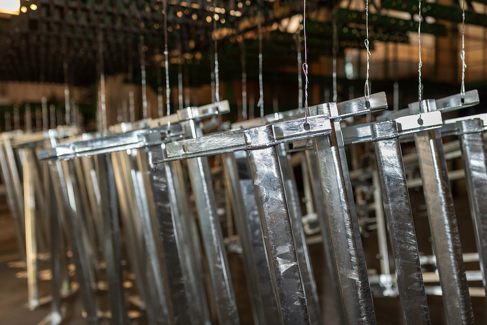 Rows of hanging pieces of metal after they have been dipped in metal finish and set out to dry