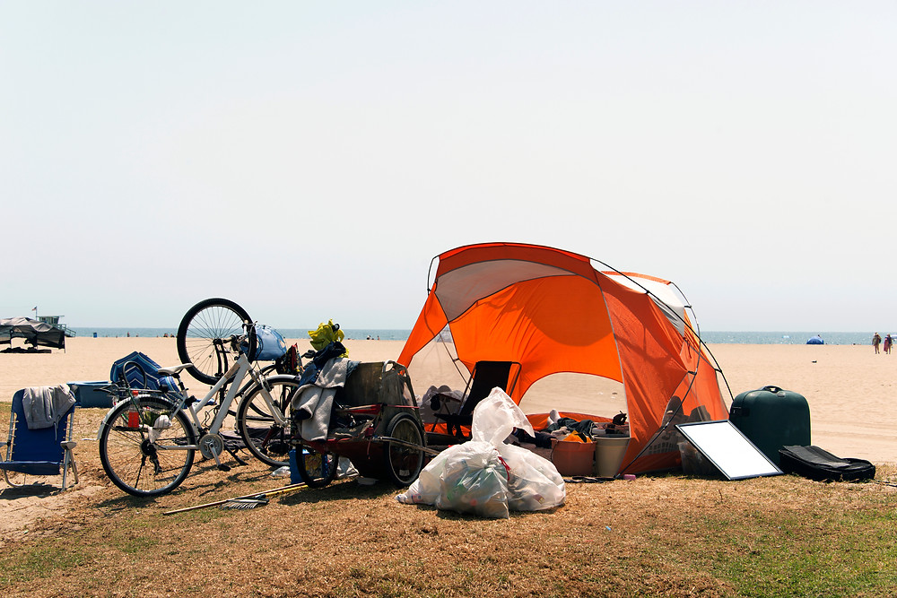 A tent, bicycle, and other personal items belonging to a homeless person at the beach