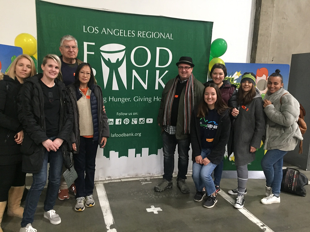 Jennifer Novak, members of her family, and others with the law firm standing in front of an L.A. Food Bank banner.