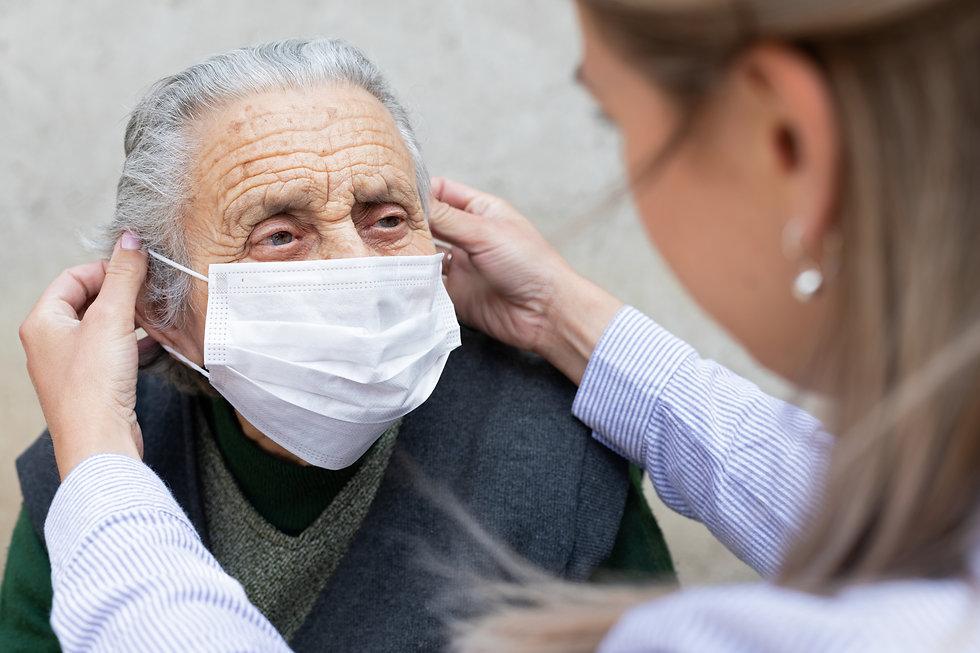 Nurse putting on surgical mask on elderl