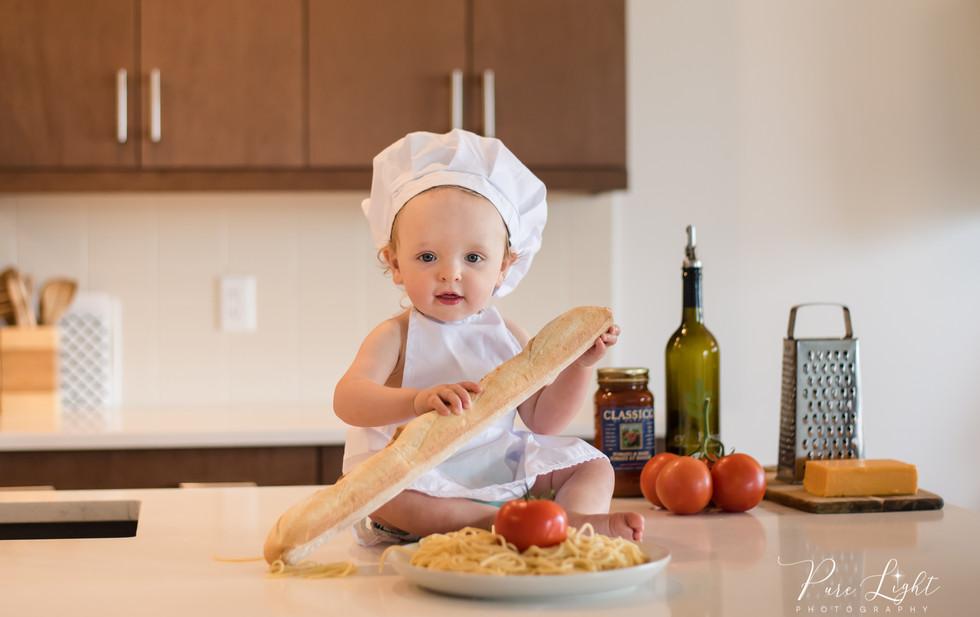toddler boy chef holding baguette