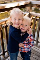 girl hugging her brother in gazebo