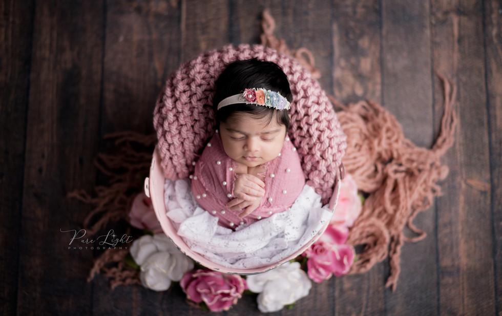 newborn baby girl in pink bucket