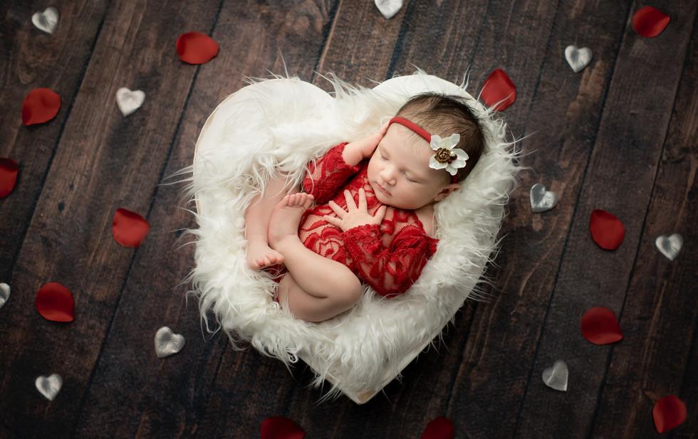 newborn baby girl in white heart bowl