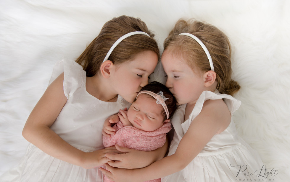 sisters hugging and kissing newborn baby girl
