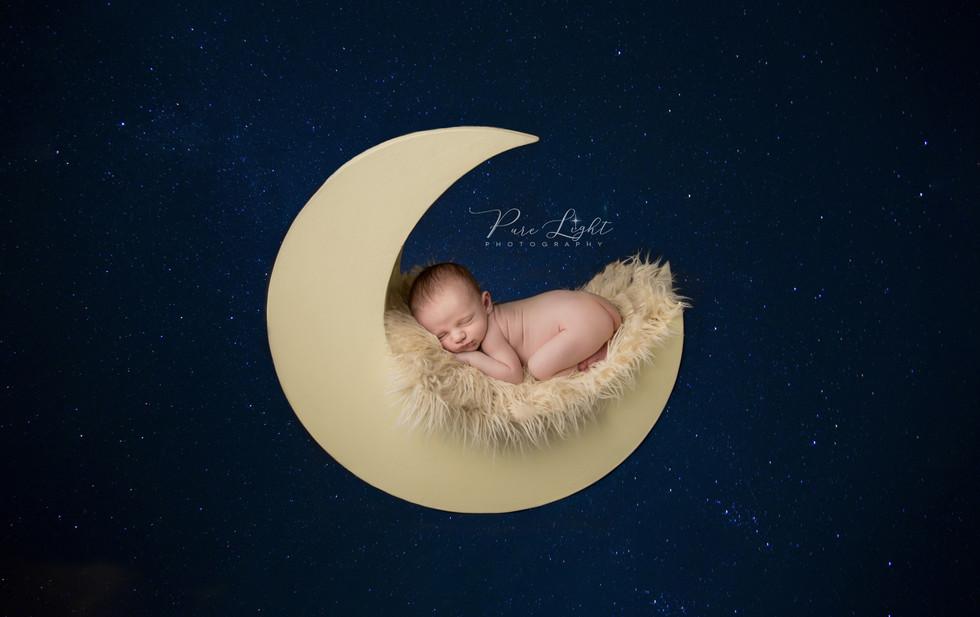 newborn baby boy sleeping on moon