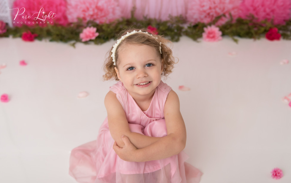 three year old girl sitting in pink dress