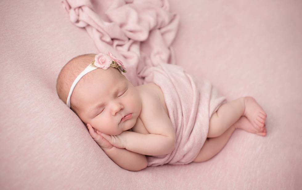 newborn baby girl asleep on side in pink