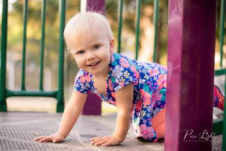 toddler girl crawling in playground