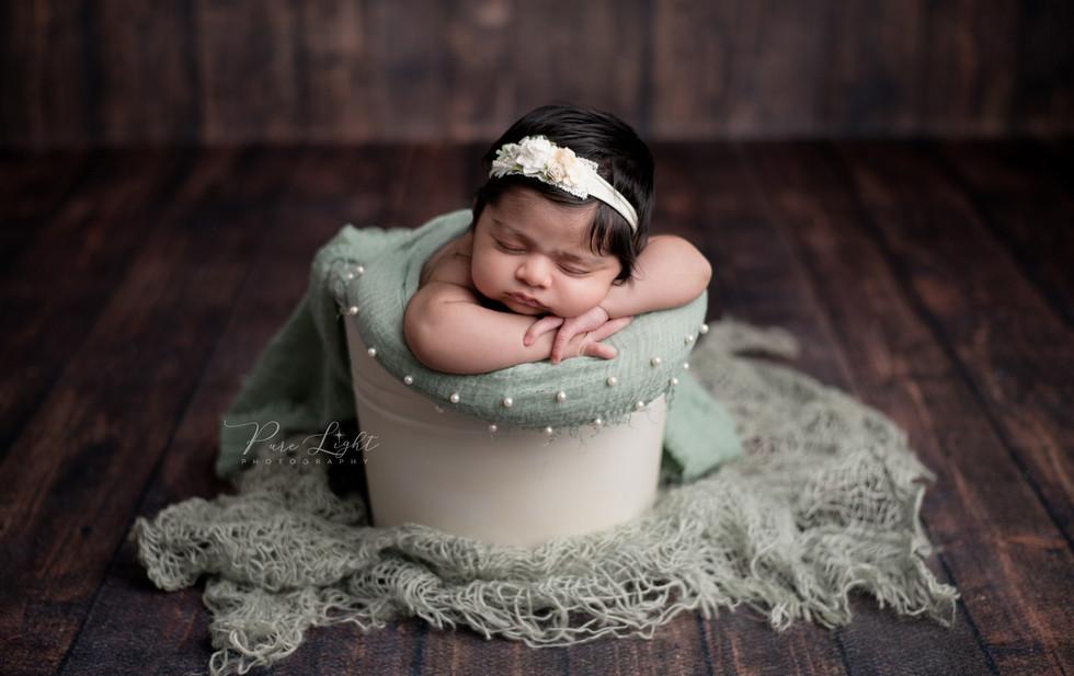 newborn baby girl in green asleep in bucket