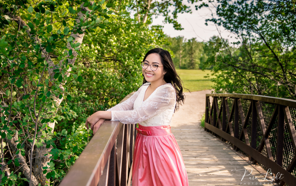 female grad on bridge