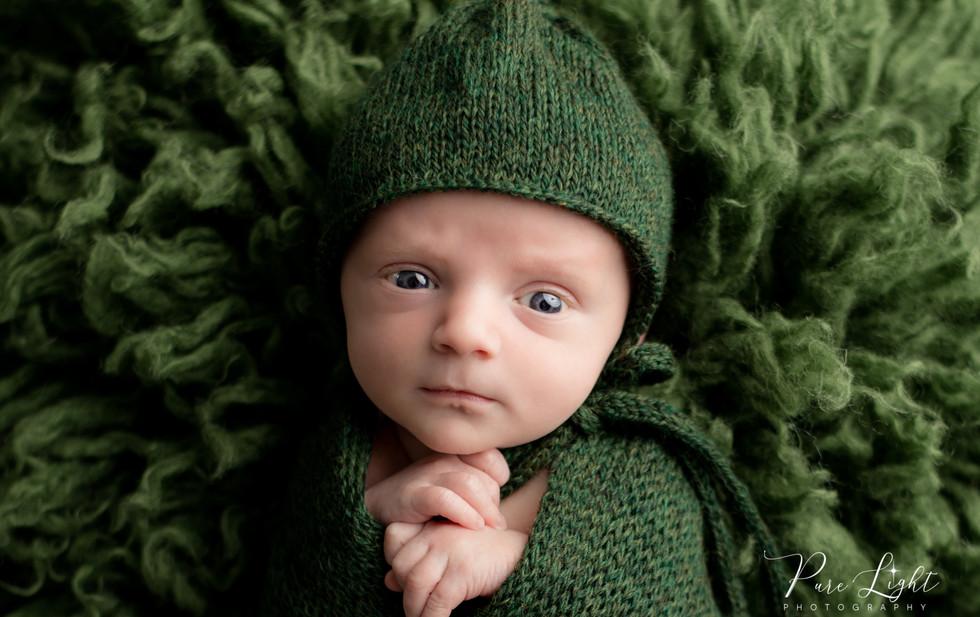 newborn baby boy awake in green wrap