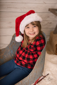 girl with Santa hat on sleigh