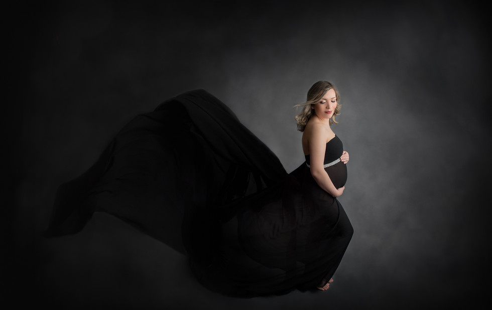 expectant mom in black fabric with big train