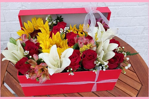 A box with roses and other flowers, roses, lilies and sunflowers.