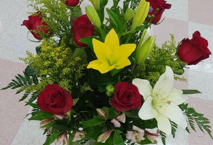 Yellow, white lilies and roses, crystal vase arrangement.