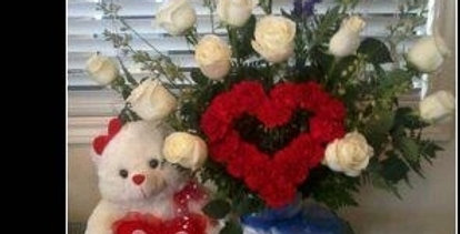 Big size white roses arrangement and a carnations heart in the center, plus teddy bear