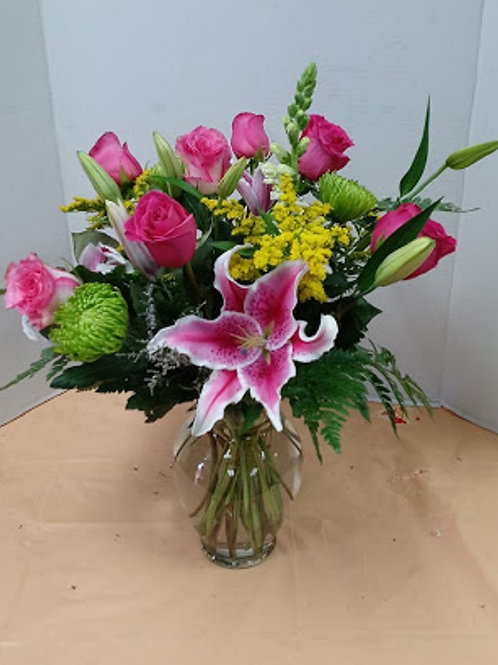 pink design online, pink roses and lilies among other flowers in a crystal vase.