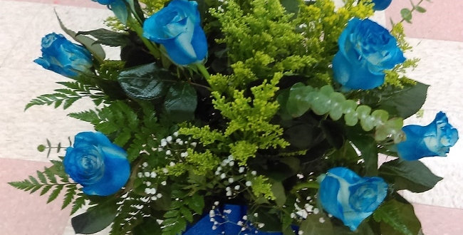 Blue long stem roses in a crystal vase with fillers and greens.