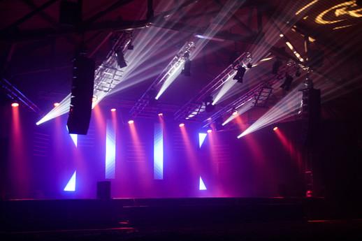 Ceci est une image d'une scène avec des projecteurs, des haut-parleurs, des praticables et