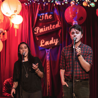 """A still from a performance at """"Theatre Pub at the Painted Lady"""" at the Painted Lady in Toronto. Featuring Alicia D'Ariano and I telepathically syncing up our bodily movements while we sing."""