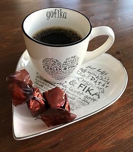 Stor kaffekopp med kaffe i, stående på assiette formad som ett hjärta. Båda med kärleksfulla, positiva och goda ord. I koppen står det också Gofika och på assietten, framför koppen, ligger det två chokladtryfflar inslagna i brunt skimrande papper.