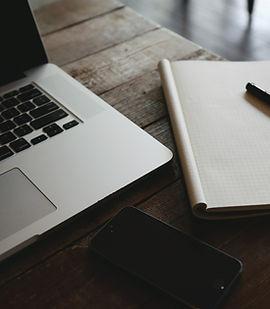 Dator, mobiltelefon, anteckningsblock och penna på ett bord i trä