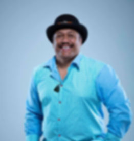 man in blue dress shirt smiling with hat