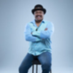 Rudi Robinson sitting on stool with arms folded smiling