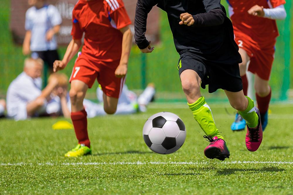 שחקני כדורגל על המגרש רצים אחרי הכדור