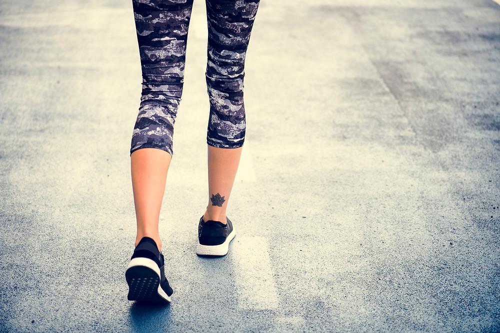אשה בנעלי ספורט צועדת על הכביש