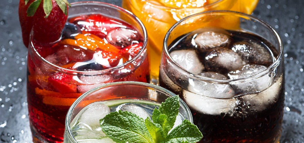assortment of iced fruit drinks on a dark background, vertical, top view, closeup