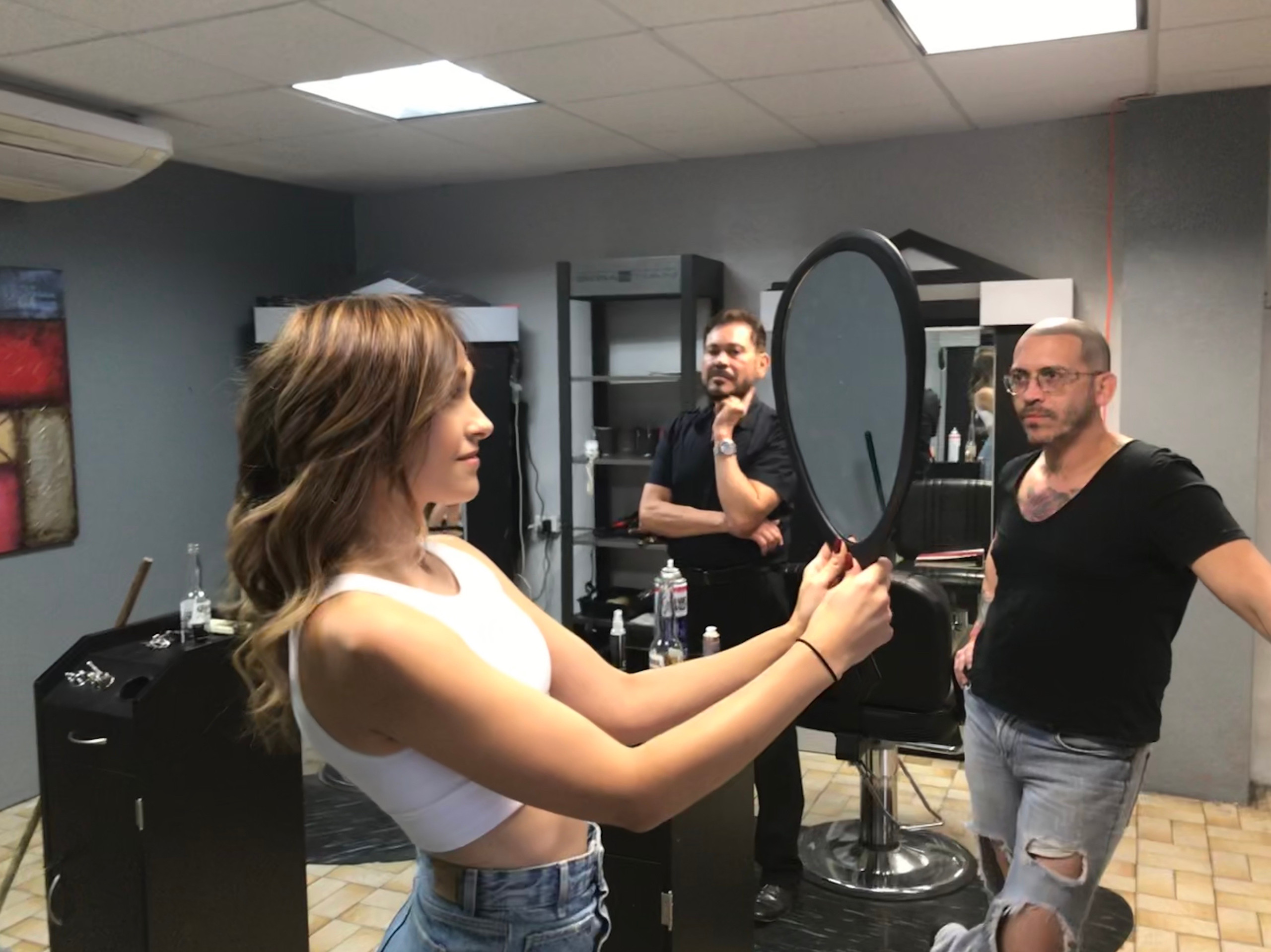 Woman looks at hair style in mirror