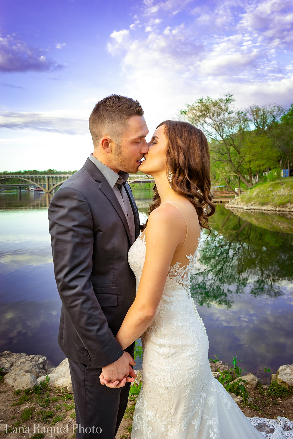 Bride and Groom Kiss at Sunset by Lake