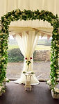 8 feet tall Wedding Archway covered in beautiful silk flowers and green foliage. completed by tiny LED lights