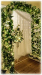 Wedding Archay wth pedestal flower arrangement underneat the archway